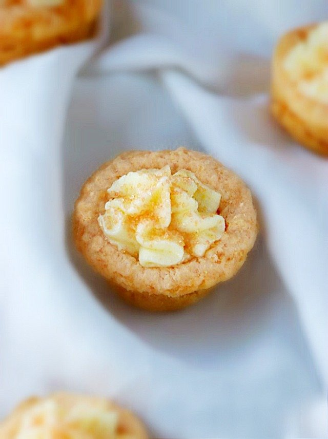 An Orange Creamsicle Cookie Cup with a light and fluffy orange topping